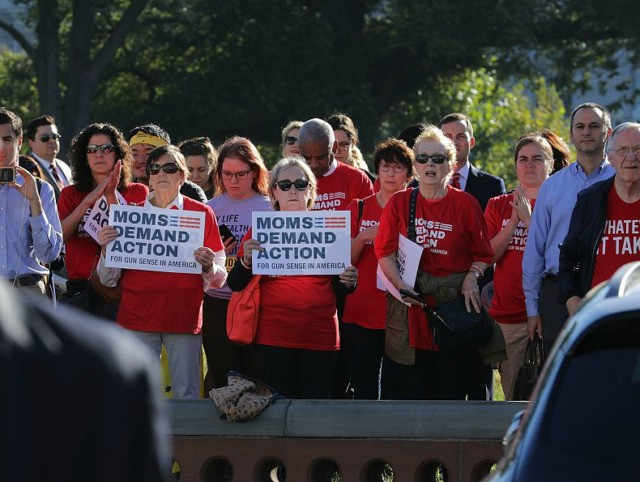 WASHINGTON, DC - OCTOBER 04: Anti-gun violence activists from Moms Demand Action stand at a distance as House Democrats rally on the East Front steps of the U.S. House of Representatives October 4, 2017 in Washington, DC. The Democratic members of Congress held the rally to honor the victims of …