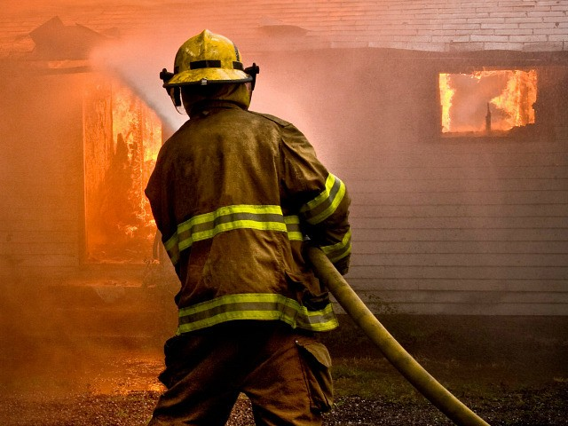 Firefighter spraying water at a house fire - stock photo