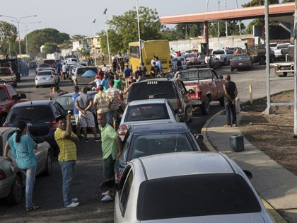 People line the street with their vehicles as they wait to fill up with gas at a fuel station, top right, in Cabimas, Venezuela, Wednesday, May 15, 2019. U.S. sanctions on oil-rich Venezuela appear to be taking hold, resulting in mile-long lines for fuel in the South American nation's second-largest …