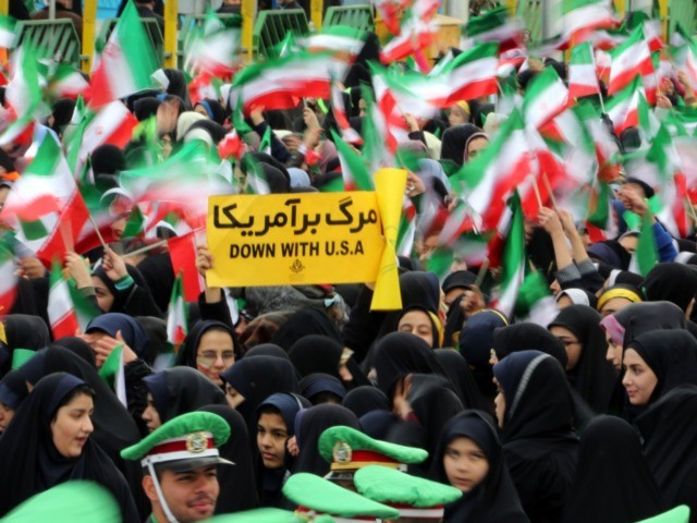 Iranian schoolgirls wave their national flag and hold an anti-US slogan during celebrations in Tehran's Azadi Square (Freedom Square) to mark the 37th anniversary of the Islamic revolution on February 11, 2016. / AFP / ATTA KENARE (Photo credit should read ATTA KENARE/AFP via Getty Images)
