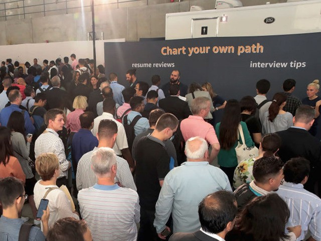 CHICAGO, ILLINOIS - SEPTEMBER 17: Job seekers wait in line to speak with Amazon recruiters and other company volunteers about job opportunities at Amazon during a career fair held at Vertiport Chicago on September 17, 2019 in Chicago, Illinois. The event was one of several Amazon career fairs held across …