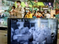 OPSHOT - People with protective face masks pass in front of a thermal scanner as they enter a shopping mall in Bangkok on January 29, 2020. - Thailand has detected 14 cases so far of the novel coronavirus, a virus similar to the SARS pathogen, an outbreak which began in …