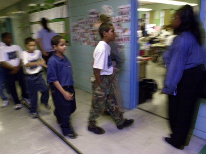 "379693 13: Students at ""Knowledge is Power Program"" (KIPP) Academy walk in strict formation into class October 4, 2000 in The Bronx, New York. The Knowledge Is Power Program educates 200 middle-school students, mostly poor black and Latino neighborhood children, housed in a hallway on the fourth floor of a …"