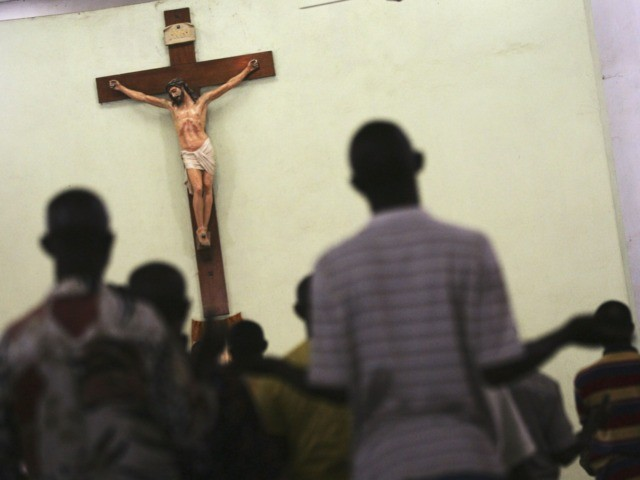 KANO, KANO - APRIL 12: Nigerian Catholic worshippers stand and pray during morning mass April 12, 2005 in Kano, Nigeria. Kano is part of Nigeria's primarily Muslim north, but devoted Catholic minority participates in frequent Masses in local cathedrals. Cardinal Francis Arinze of Nigeria is considered a leading contender to …