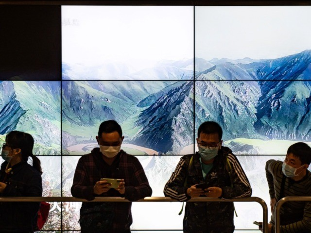 People wearing facemasks queue at the West Kowloon rail station in Hong Kong on January 23, 2020. - The international finance hub has been on high alert for the mystery SARS-like virus ever since it first emerged within the Chinese city of Wuhan, killing 17 people so far. (Photo by …