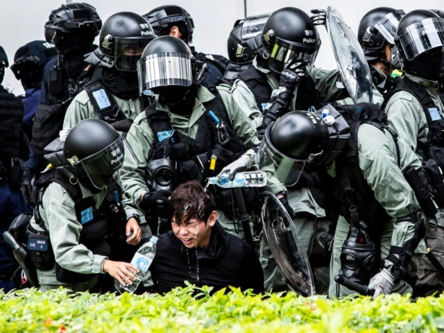 OPSHOT - A man (C) has pepper spray washed from his his face by police after being detained during a clearance operation after a demonstration against parallel trading in Sheung Shui in Hong Kong on January 5, 2020. - In recent years Sheung Shui has been swamped by a huge …