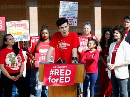 Music teacher Noah Karvelis, center, who helped organize Arizona Educators United, speaks at a news conference at the Esperanza Elementary School in Isaac School District speaking on teacher pay and school funding Wednesday, April 25, 2018, in Phoenix. Arizona teachers are scheduled to go on strike Thursday. (AP Photo/Ross D. …