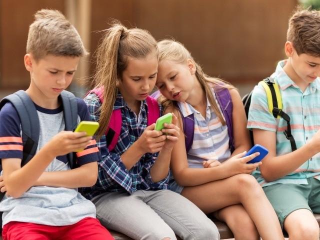 schoolkids using smartphones