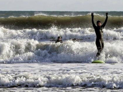 Democratic presidential candidate U.S. Rep. Tulsi Gabbard, D-Hawaii, surfs in the Atlantic Ocean, Wednesday, Jan. 1, 2020, in Hampton, N.H. (AP Photo/Cheryl Senter)
