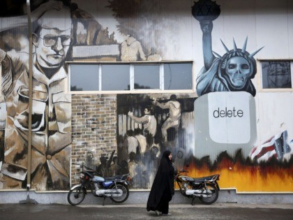 "An unidentified woman walks under an anti-U.S. graffiti painted on the walls of the former U.S. Embassy in Tehran, Iran, Saturday, Nov. 2, 2013. Iran's hardliners unveiled two new ""Death to America"" songs at the site of the former U.S. embassy in Tehran Saturday to keep the anti-U.S. sentiments alive. …"
