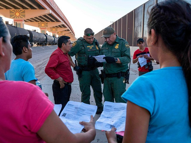 TOPSHOT - US Customs and Border Protection agents check documents of a small group of migrants, who crossed the Rio Grande from Juarez, Mexico, on May 16, 2019, in El Paso, Texas. - About 1,100 migrants from Central America and other countries are crossing into the El Paso border sector …