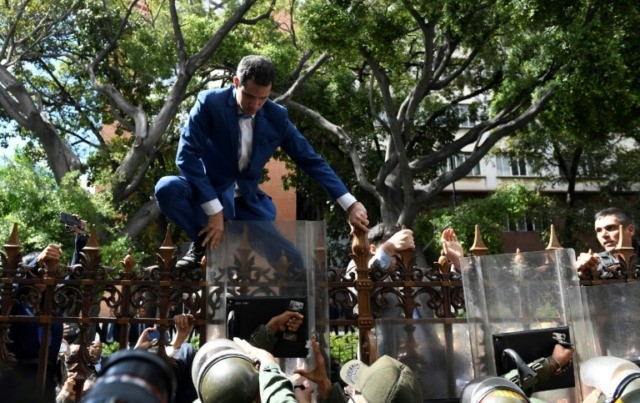 Venezuelan opposition leader and self-proclaimed acting president Juan Guaido is pushed back by police with riot shields as he tries access the National Assembly compound