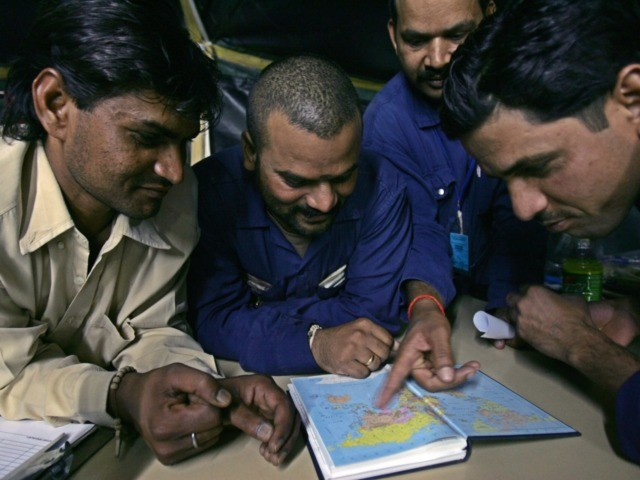 Baghdad, IRAQ: Immigrant workers look at a map of the world to locate Iraq at a US army base in Mahmudiyah in the southern outskirts of Baghdad, early December 2005. Some 6,000 to 7,000 immigrants from India, Sri Lanka, and Philippines work on US Army bases in Iraq for a …