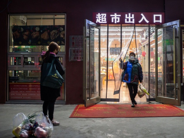 A woman (R) wearing a protective facemask to help stop the spread of a deadly virus which began in Wuhan, leaves a supermarket holding her groceries as her friend (L) waits for her in Beijing on January 29, 2020. - The number of confirmed cases in the new virus outbreak …