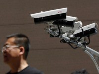People walk by Chinese-made surveillance cameras installed along a street in Beijing, Thursday, May 23, 2019. The Chinese video surveillance company Hikvision says it is taking concern about the use of its technology seriously following a report that the U.S. may block several Chinese surveillance companies from buying American components. …