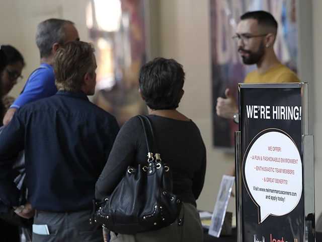 A sign advertises jobs at Neiman Marcus Last Call during a job fair at Dolphin Mall, Tuesday, Oct. 1, 2019, in Miami. (AP Photo/Lynne Sladky)
