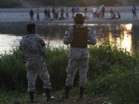 Mexican National Guards stand on the Mexican side of the Suchiate River near Ciudad Hidalgo, Mexico, where they watch Central American migrants standing on the Guatemalan side of the river, early Wednesday, Jan. 22, 2020. The number of migrants stuck at the Guatemala-Mexico border continued to dwindle Wednesday as detentions …