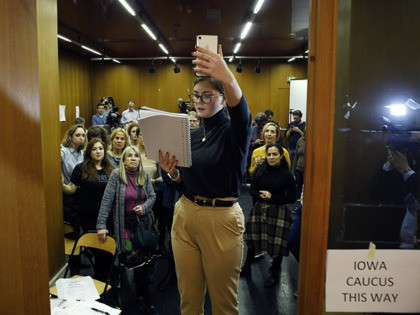 Emily Hagedorn, center, gives a phonecall to announce the election results, in Paris, Monday, Feb. 3, 2020. Paris is one of just three satellite caucus locations outside the U.S., and drew the biggest number of expat Iowans. (AP Photo/Thibault Camus)