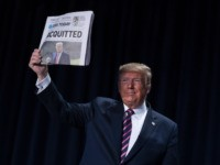 "President Donald Trump holds up a newspaper with the headline that reads ""ACQUITTED"" during the 68th annual National Prayer Breakfast, at the Washington Hilton, Thursday, Feb. 6, 2020, in Washington. (AP Photo/ Evan Vucci)"