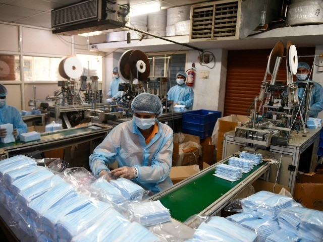 A worker packs protective facemasks at a production facility in the outskirts of Ahmedabad on February 3, 2020. - China said on February 3 it urgently needed medical equipment and surgical masks as the death toll from a new coronavirus jumped above 360, making it more deadly than the SARS …