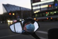 BEIJING, CHINA - FEBRUARY 22: A Chinese man is seen in the side mirror of his scooter as he wears a protective mask while waiting at a red light on February 22, 2020 in Beijing, China. The number of cases of the deadly new coronavirus COVID-19 being treated in China …