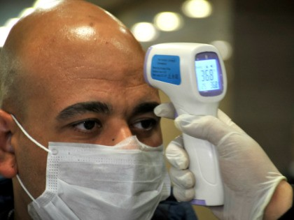 "Egyptian Quarantine Authority employees scan body temperature for an incoming traveller at Cairo International Airport on February 1, 2020, amidst efforts to detect possible cases of SARS-like ""Wuhan coronavirus"" (novel coronavirus 2019-nCoV). (Photo by - / AFP) (Photo by -/AFP via Getty Images)"