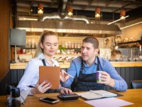 Young man and woman going through paperwork together in their restaurant. Small family restaurant owners discussing finance calculating bills and expenses of their small business.