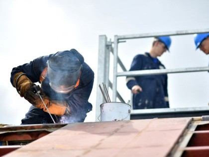 """A welder works on a boat at Mainstay Marine Solutions' shipyard in Milford Haven in Wales on August 21, 2019. - Welsh businessman Stewart Graves is certain that a no-deal Brexit will shut down his marine renewable energy plant currently testing its prototypes in the Irish Sea. """"We are world …"""