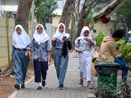 A group of young Muslims wearing hijabs make their way along a street in Jakarta on September 19, 2019. - Indonesia is set to vote on a plan to outlaw gay and pre-marital sex while beefing up its blasphemy laws in a shakeup fuelled by religious conservatism and slammed by …