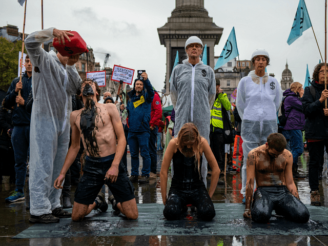 LONDON, ENGLAND - OCTOBER 12: Extinction Rebellion activists pour fake oil over each other as they continue to demonstrate for the sixth day running in Trafalgar Square on October 12, 2019 in London, England. The climate change activists have blockaded various central locations around Westminster and police continue to arrest …