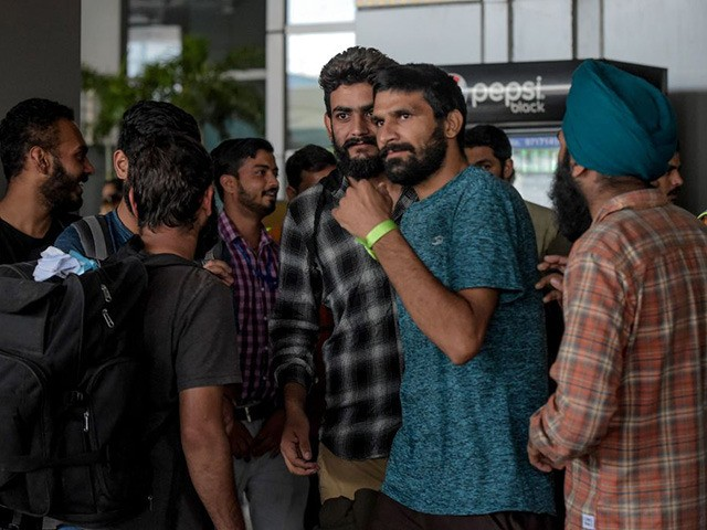 Indian nationals arrive at Indira Gandhi International airport in New Delhi on October 18, 2019, after being deported from Mexico as they tried to enter the United States. - A total of 311 Indians who paid tens of thousands of dollars each trying to get into the United States arrived …