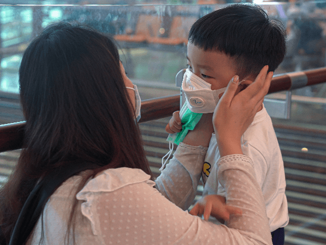 A woman wearing a mask helps her son put on his mask at Changi Airport on January 25, 2020 in Singapore. Yesterday Singapore confirmed its third case of the deadly coronavirus which emerged last month in the city of Wuhan in China. (Photo by Ore Huiying/Getty Images)