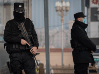 In this picture taken on January 27, 2020 police officers wearing protective facemasks to help stop the spread of a deadly virus which began in Wuhan, secure an area at the Beijing railway station. - The deadly new coronavirus that has broken out in China, 2019-nCoV, will afflict a minimum …