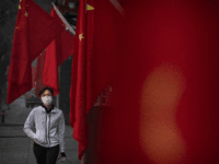 A woman wears a protective mask as she walks by Chinese flags in a street during the Chinese New Year and Spring Festival holiday on January 28, 2020 in Beijing, China. The number of cases of a deadly new coronavirus rose to over 4000 in mainland China Tuesday as health …