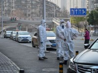 This photo taken on January 30, 2020 shows officials in protective suits gathered on a street after an elderly man wearing a facemask (not pictured) collapsed and died on the pavement near a hospital in Wuhan. - AFP journalists saw the body on January 30, not long before an emergency …