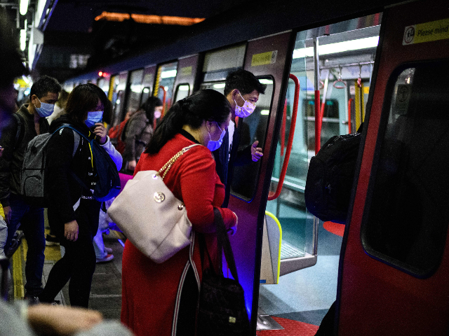 Passengers wear protective face masks as they board a Hong Kong bound MTR train to Hong Kong at Lo Wu MTR station hours before the closing of the Lo Wu border crossing in Hong Kong, on February 3, 2020, amid an outbreak of a coronavirus which began in the Chinese …