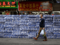 A man wearing a protective face mask walks past stacks of toilet paper for sale in the Tsuen Wan district of Hong Kong on February 8, 2020. - Hong Kong has been hit by a wave of panic-buying in recent days with supermarket shelves frequently emptied of crucial goods such …