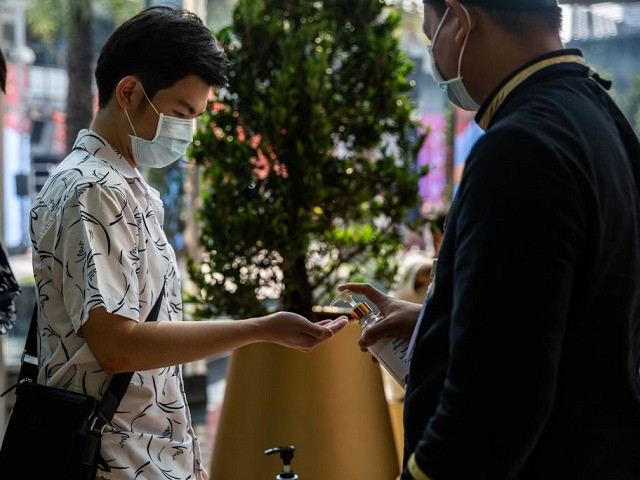 People wearing face-masks visit a hand sanitizer station at Siam Paragon Mall on February 8, 2020 in Bangkok, Thailand. As Thailand confirms its 32nd case of the 2019 Novel Coronavirus and face mask supplies dwindle in stores, Thailand's Ministry of Defence assigned the Army's Medical Department, Phramongkutklao Hospital and the …