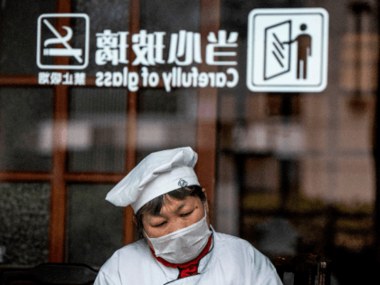 A restaurant employee has a rest at a table in Shanghai on February 8, 2020. - The new coronavirus that emerged in a Chinese market at the end of last year has killed more than 700 people and spread around the world. (Photo by NOEL CELIS / AFP) (Photo by …