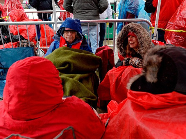 People line up in the rain and icy weather outside the SNHU arena hours ahead of President Trump's rally in Manchester, New Hampshire on February 10, 2020. - The state is especially in the spotlight this year after Iowa's caucus, in which participants publicly display their support for a candidate …