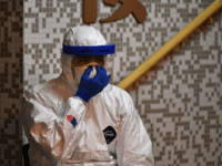 A medical personnel wearing a protective suit checks his mask as he waits near a block's entrance in the ground of a residential estate, in Hong Kong, early on February 11, 2020, after two people in the block were confirmed to have contracted the coronavirus according to local newspaper reports. …