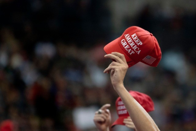Supporters hold up MAGA hats as US President Donald Trump speaks during a rally in Manchester, New Hampshire on February 10, 2020. (Photo by JIM WATSON / AFP) (Photo by JIM WATSON/AFP via Getty Images)