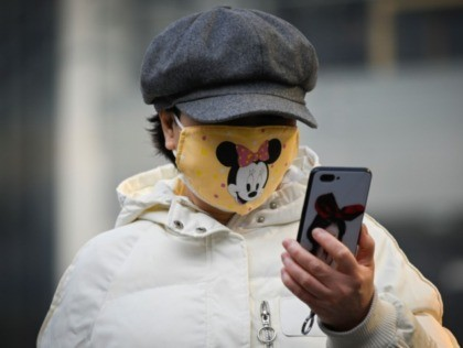 A woman wearing a Minnie Mouse face mask looks at her mobile phone in Beijing on February 11, 2020. - The death toll from a new coronavirus outbreak surged past 1,000 on February 11 as the World Health Organization warned infected people who have not travelled to China could be …