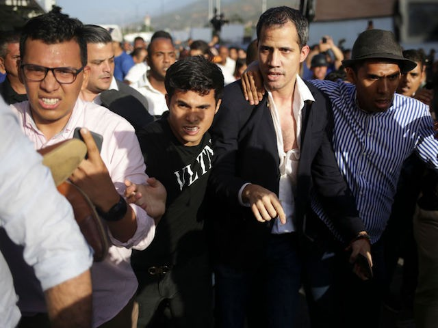 TOPSHOT - Venezuelan opposition leader and self-proclaimed acting president Juan Guaido is escorted to his car after arriving at Simon Bolivar International Airport in Maiquetia, Vargas state, Venezuela on February 11, 2020. - Guaido returned to Venezuela after a 23-day international tour to revitalize pressure on President Nicolas Maduro, his …