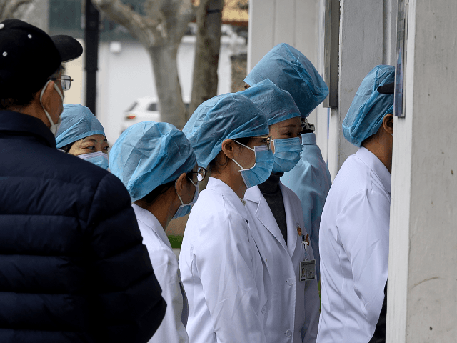 Nurses wearing protective face masks enter a community hospital in Shanghai on February 13, 2020. - China's official death toll and infection numbers from the deadly COVID-19 coronavirus spiked dramatically on February 13 after authorities changed their counting methods, fuelling concern the epidemic is far worse than being reported. (Photo …