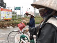 Local residents wearing protective facemasks amid concerns of the COVID-19 coronavirus wait to pass through a checkpoint in Son Loi commune in Vinh Phuc province on February 13, 2020. - Villages in Vietnam with 10,000 people close to the nation's capital were placed under quarantine on February 13 after six …