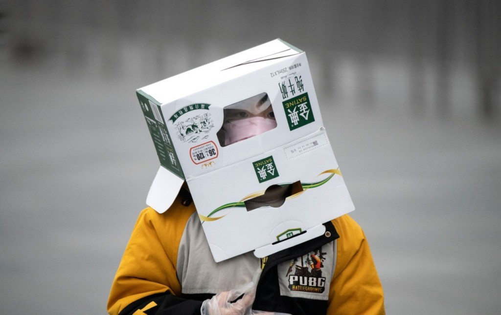 TOPSHOT - A boy wears a cardboard box on his head at the Shanghai Railway station in Shanghai on February 13, 2020. - The number of deaths and new cases from China's COVID-19 coronavirus outbreak spiked dramatically on February 13 after authorities changed the way they count infections in a move that will likely fuel speculation that the severity of the outbreak has been under-reported. (Photo by NOEL CELIS / AFP) (Photo by NOEL CELIS/AFP via Getty Images)