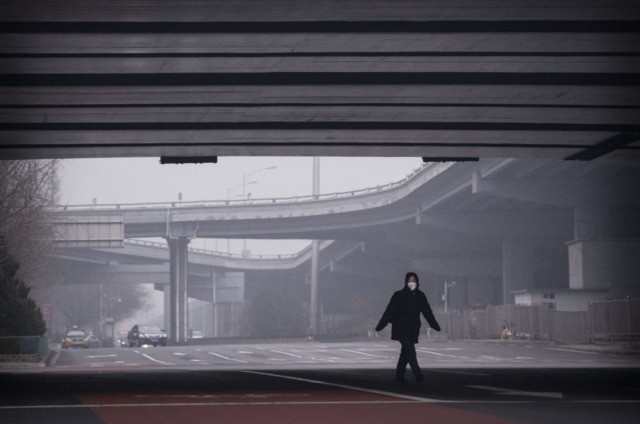 BEIJING, CHINA - FEBRUARY 13: A Chinese woman wears a protective mask as she crosses a nearly empty intersection on February 13, 2020 in Beijing, China. The number of cases of the deadly new coronavirus COVID-19 rose to more than 52000 in mainland China Thursday, in what the World Health …