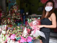 A vendor wearing a protective facemask stands at their shop on Valentine's day at a flower market in Manila on February 14, 2020, as the Philippines battles the COVID-19 illness, with its ground zero in Wuhan China. (Photo by Ted ALJIBE / AFP) (Photo by TED ALJIBE/AFP via Getty Images)
