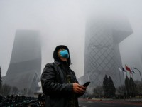 BEIJING, CHINA - FEBRUARY 13: A Chinese man wears a protective mask as he stands near the CCTV building in fog and pollution during rush hour in the central business district on February 13, 2020 in Beijing, China. The number of cases of the deadly new coronavirus COVID-19 rose to …
